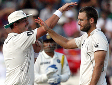 New Zealand's captain Daniel Vettori celebrates with Jesse Ryder after the dismissal of Sehwag on Saturday
