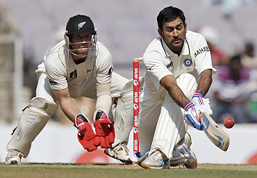 Mahendra Singh Dhoni plays the sweep shot as New Zealand's wicketkeeper Gareth Hopkins looks on