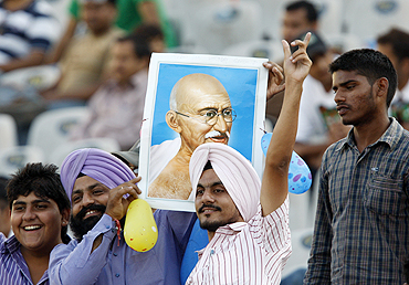Indian fans hold up a portrait of Mahatma Gandhi and sing in the stands on the occassion of Gandhi Jayanti in Mohali on Saturday