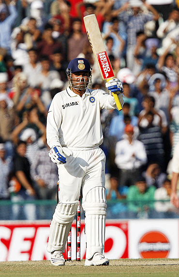 Virender Sehwag raises his bat to the pavilion after scoring 50