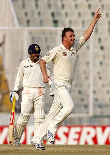 Doug Bollinger celebrates after dismissing Rahul Dravid as Virender Sehwag looks on