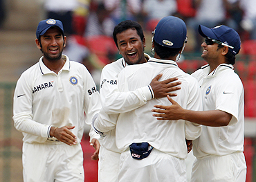 Praghyan Ojha celebrates with teammates after scalping the wicket of Shane Watson