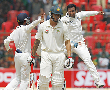 Pragyan Ojha (right) celebrates after dismissing Mitchell Johnson (centre)
