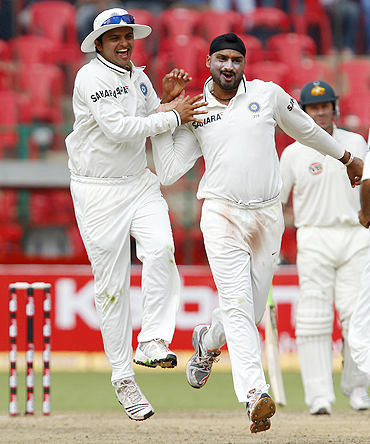 Harbhajan Singh celebrates with Suresh Raina after claiming the wicket of Simon Katich