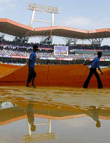 Grounds staff remove covers at Kochi stadium