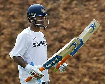 MS Dhoni checks his bat during a practice session i