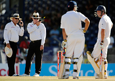 Umpires Daryl Harper (left) and Russell Tiffin wait for a referral verdict on England's Andrew Strauss (right), during a Test match in the West Indies earlier this year