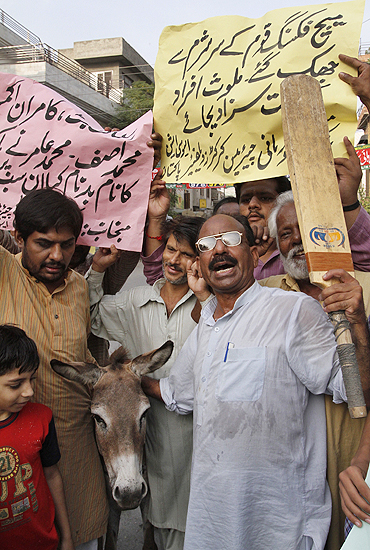 Pakistani cricket fans pose with a donkey as they hold placards and shout slogans against national players involved in a match fixing scandal in Lahore