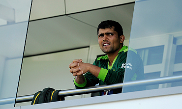 Kamran Akmal watches from the players' balcony at Somerset
