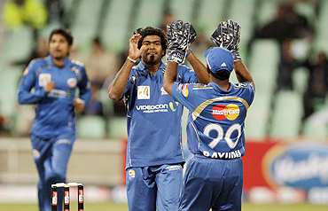 Mumbai Indians Lasith Malinga (centre) and Ambati Rayudu celebrate the wicket of Guyana's Sewnarine Chattergoon