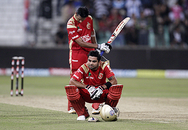 Royal Challengers Bangalore's Virat Kohli (foreground) and Rahul Dravid wear a dejected look after losing to Mumbai Indians
