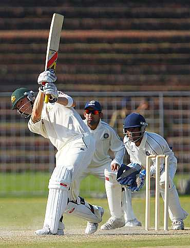 Australia's Michael Clarke plays a shot as Gautam Gambhir and Wridhimman Saha of the Board President's XI look on in their match in Chandigarh