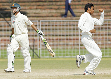 Ricky Ponting (left) walks off the field after being dismissed by Jaidev Unadkat