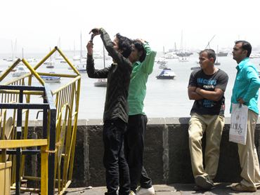 Tourists try to take a picture of the Gateway of India from afar