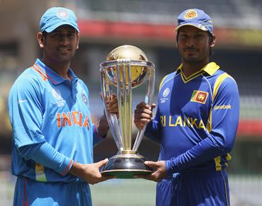 Captains MS Dhoni  and Kumar Sangakkara pose with the ICC World Cup ahead of Saturday's final