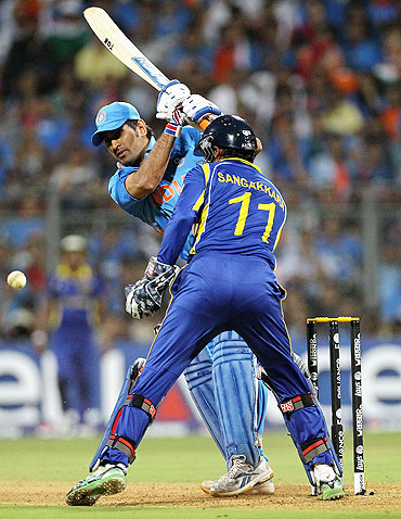 Mahendra Singh Dhoni plays the ball fine as Kumar Sangakkara looks on