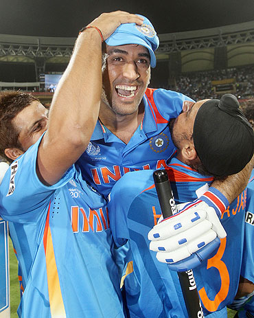 MS Dhoni (centre) celebrates victory with teammates Suresh Raina (left) and Harbhajan Singh