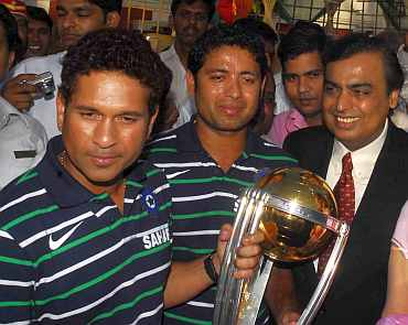 Sachin Tendulkar with the World Cup trophy along with Mukesh Ambani