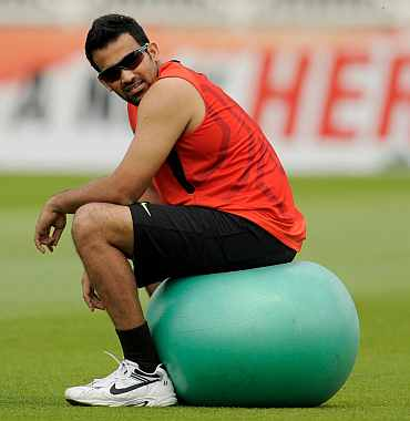 India's Zaheer sits on a ball during a training session