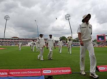 Indian players walk back to the pavillion after bad light stopped play