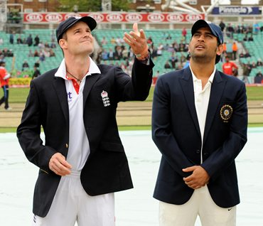 England captain Andrew Strauss (L) tosses the coin, as India's captain Mahendra Singh Dhoni calls before the fourth and final Test at The Oval ground in London