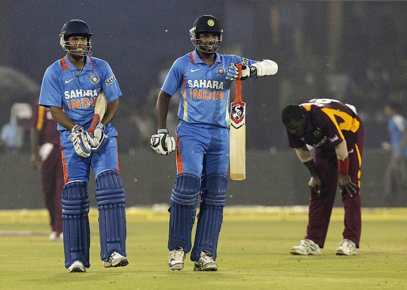 West Indies's captain Darren Sammy (right) reacts as India's Varun Aaron (centre) and Umesh Yadav celebrate winning their first One-day