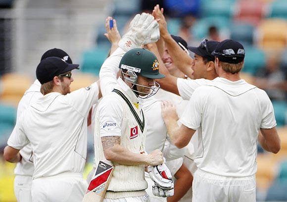 Australia's captain Michael Clarke (centre) walks past New Zealand players after losing his wicket to Doug Bracewell