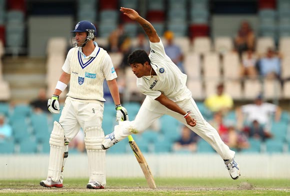 Umesh Yadav bowls as Phil Hughes looks on