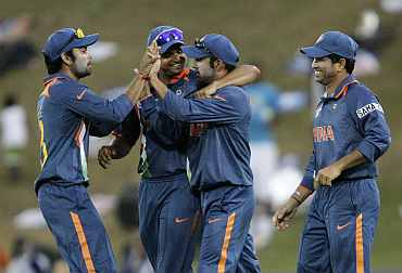 Virat Kohli celebrates with team-mates after a fall of a wicket