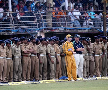 Michael Clarke with the Australian team security officer on from the boundary as a large number of police surround the field in Kochi