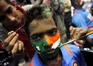 Face painters apply the colours of the Pakistani and Indian national flags to the face of a cricket fan in Mumbai