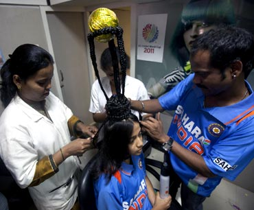 Hairdressers shape the hair of cricket fan Rajna Pandit, 22, to resemble the World Cup trophy in Mumbai