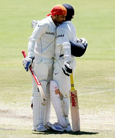 Virender Sehwag is congratulated by Sachin Tendulkar after scoring a century