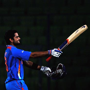 Virat Kohli raises his bat on reaching his century