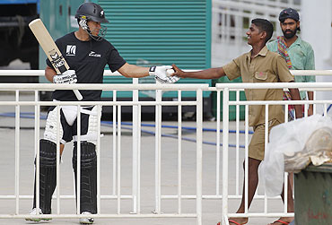 A ground worker hands over the ball to New Zealand's Rose Taylor (left) as he arrives to bat in the nets during a practice session in Chennai on Friday