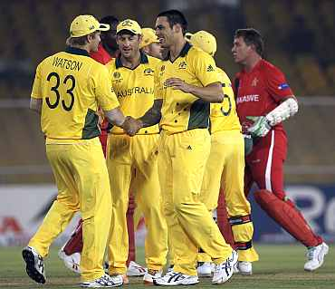 Australian players celebrate the fall of a Zimbabwe wicket