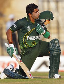 Umar Akmal kisses his cap after getting to 50