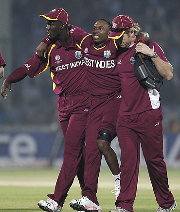 West Indies' Dwayne Bravo (centre) is helped off the field after being injured