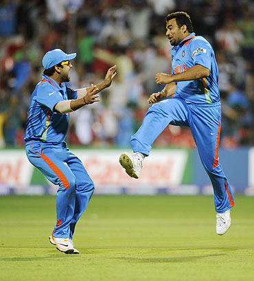 India's Zaheer Khan (right) celebrates with teammate Virat Kohli after dismissing Andrew Strauss