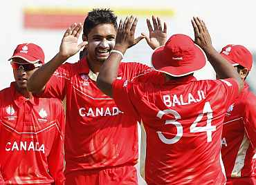 Canada's Harvir Baidwan (L) celebrates dismissing Zimbabwe's Charles Coventry