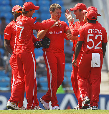 Ray Price is congratulated by teammates after dismissing Canada's Nitish Kumar