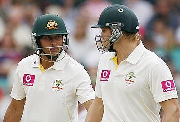 Australia's Usman Khawaja talks to Shane Watson on Monday