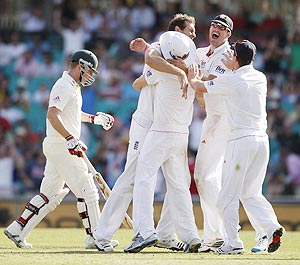 English players congratulate Chris Tremlett (centre) for taking the wicket of Australia's Brad Haddin (left) on Thursday