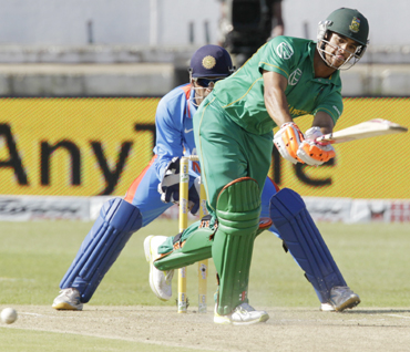 South Africa's JP Duminy plays a shot with MS Dhoni looking on during the one day international cricket match against India at Kingsmead Stadium in Durban