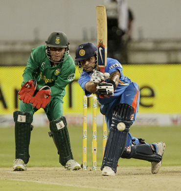 India's Virat Kholi (R) plays a shot as South Africa's wicketkeeper AB De Villiers looks on during the day international cricket match against South Africa at Kingsmead Stadium in Durban