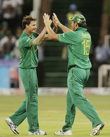South Africa's Dale Steyn (L) and Graeme Smith celebrate the wicket of India's Virat Kholi (not in picture) during the one day international cricket match at Kingsmead Stadium in Durban