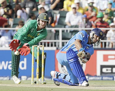 India's Yuvraj Singh plays a shot as AB De Villiers looks on