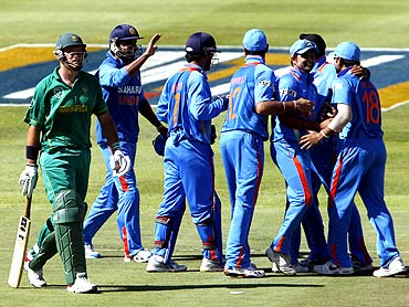 India's Murali Vijay (2nd left), MS Dhoni (3rd left), Yuvraj Singh (4th left), Suresh Raina (3rd right),  Harbhajan Singh (2nd right) and Virat Kohli (R) celebrate the wicket of South Africa's Graeme Smith (L) during their third one-day international cricket match in Cape Town