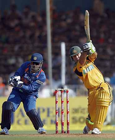 Ricky Ponting plays a shot as India's MS Dhoni looks on