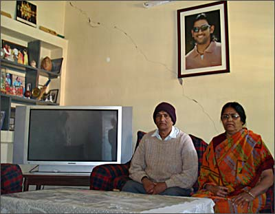 Pan and Devki Singh next to the television Dhoni bought them to watch his matches